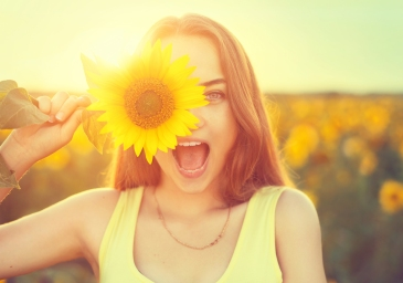 Beauty joyful teenage girl with sunflower enjoying nature and la